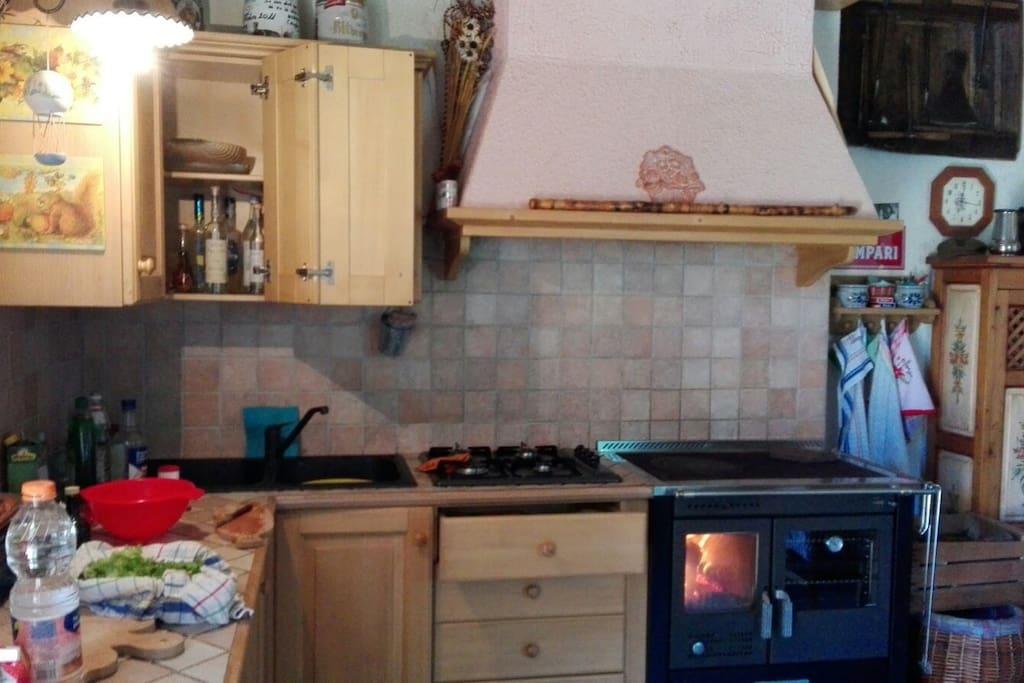 Zona cucina con stufa a legna e piano cottura a gas