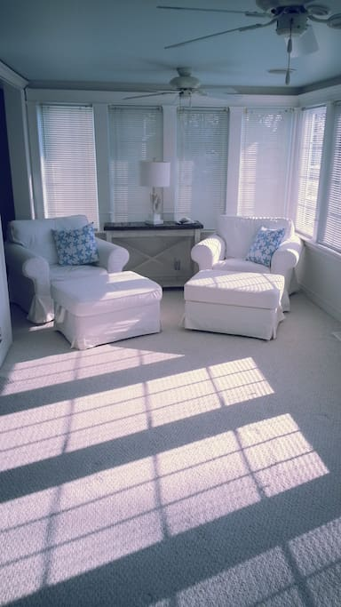 Plush furniture in the front room with light flooding in.