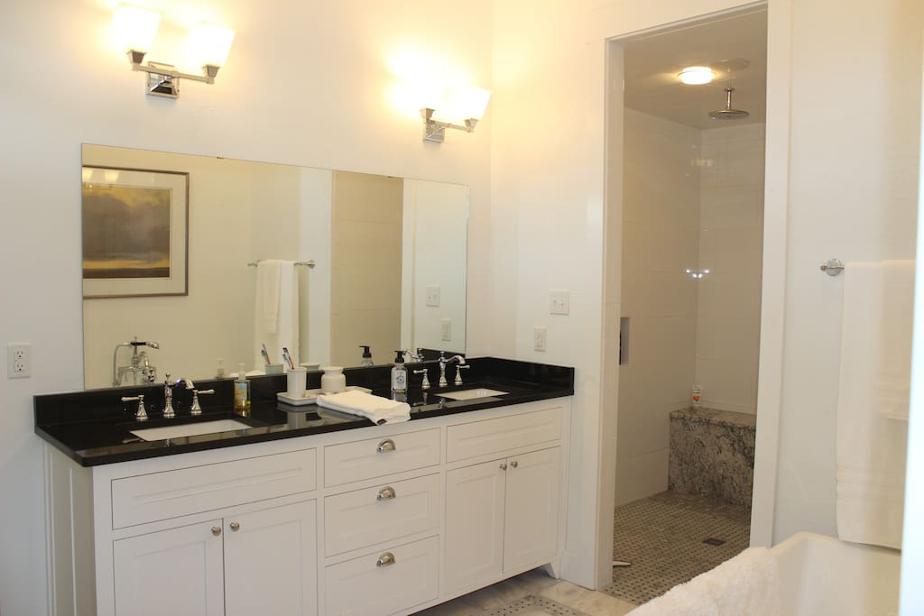 Double vanity and walk-in shower with bench and separate toilet area