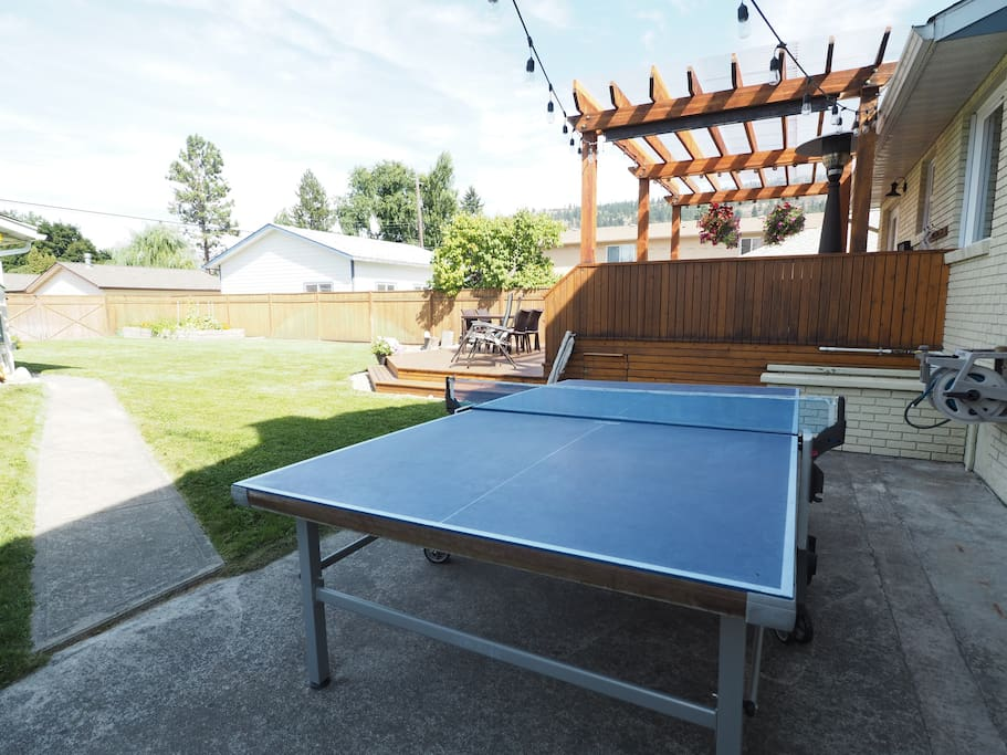 The table tennis table is situated right outside the kitchen and living room