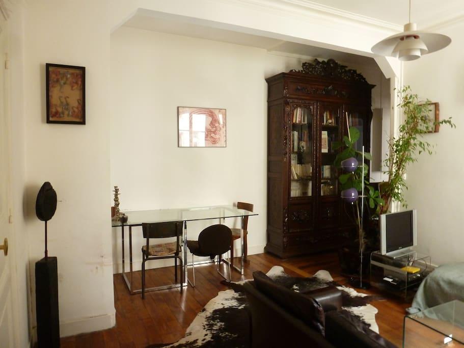 Salon: bibliothèque, plantes, table à diner, tapis...