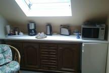 Mikrowelle, Kühlschrank,  Kaffeemaschine,  Toaster,  Wasserkocher, Microwelle, Kühlschrank, Eierkocher und Geschirrschrank.
