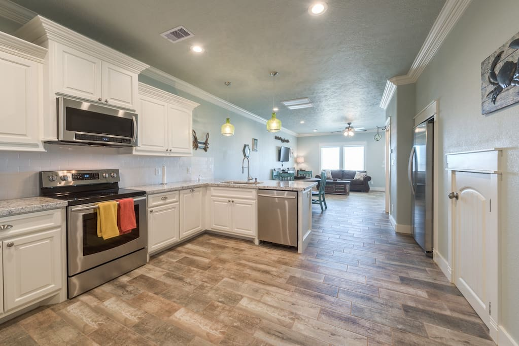 Large open kitchen, stainless steel appliances,  and eat up bar