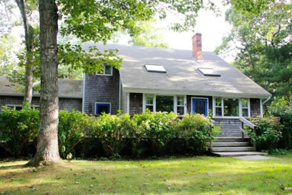 All along the front of the house, there is a large deck, complete with casual seating, a dining table, and two grills—gas and charcoal. The front of the house faces away from the road, and along with mature trees, this creates a secluded, private space. The front yard makes a lovely play space.