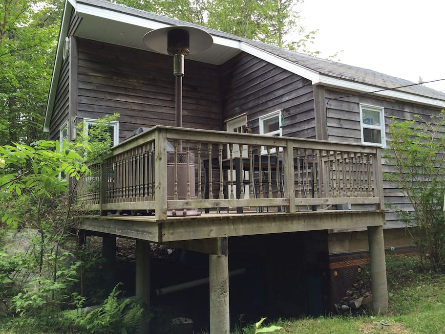 Raised private deck surrounded by trees and an adjacent brook.