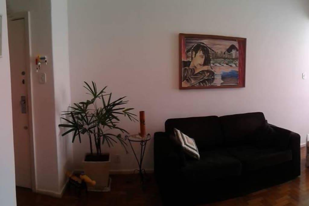 Sala com sofá cama estilo americano, tv, poltrona de massagem e ar condicionado