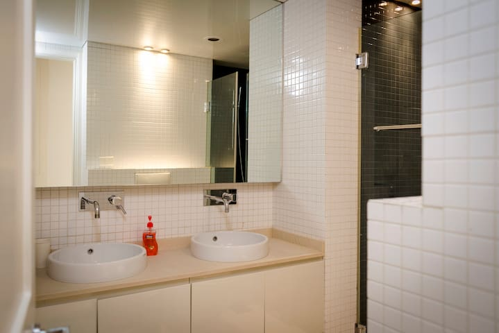 The first bathroom with wide modern shower and two sinks.