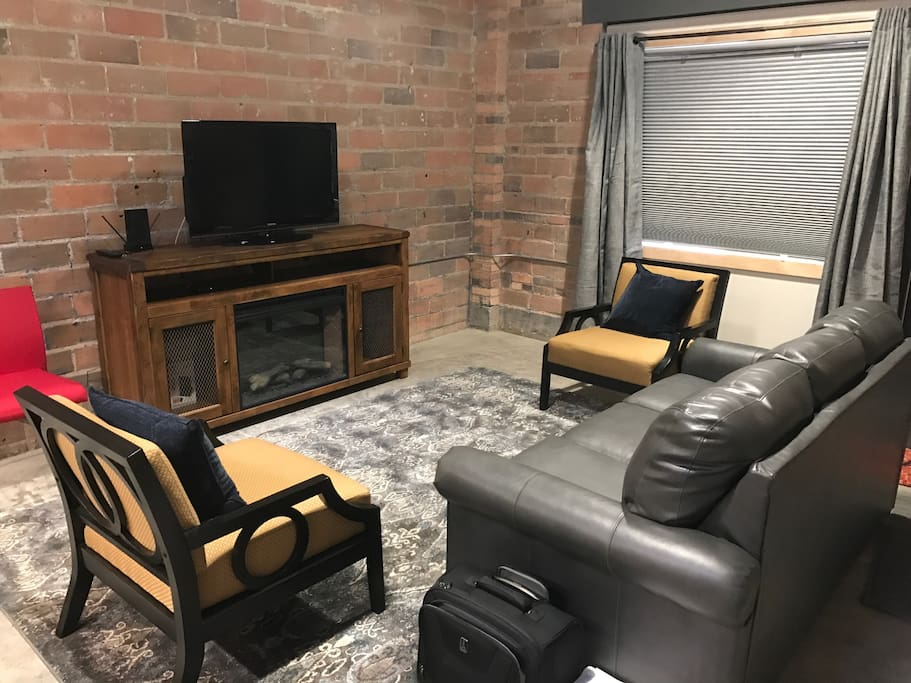 Cozy living room with full sofa sleeper, tv and a fireplace.