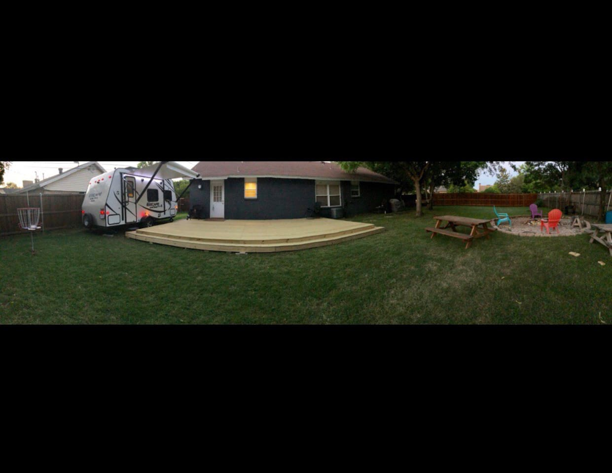 Backyard: disc golf, fire pit, camper with a deck connected and a hot tub tucked away in the corner