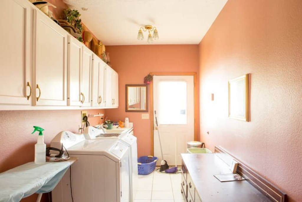 Laundry room with washer, dryer, sink and ironing board.