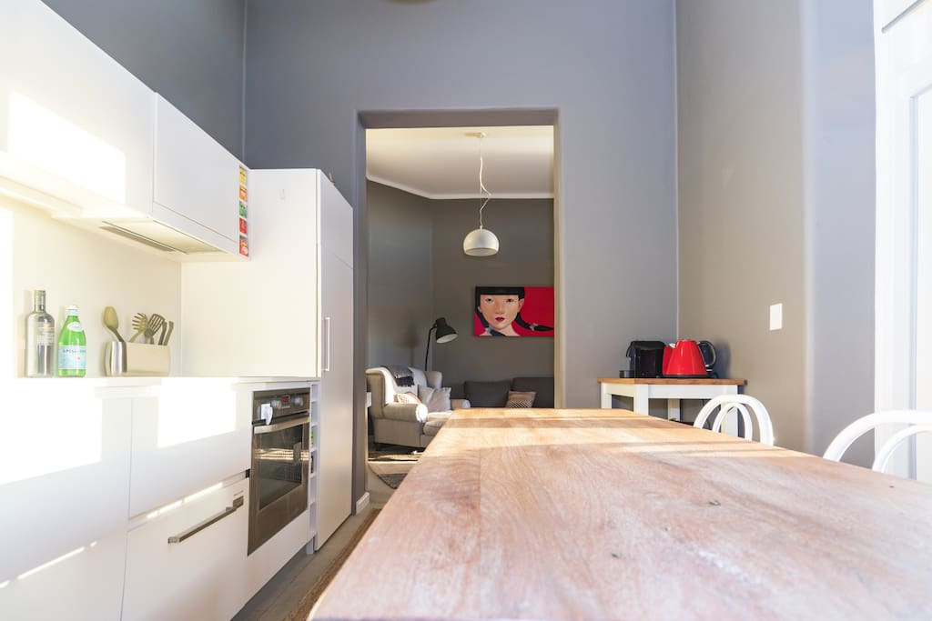 Functional kitchen and dining zone with Nespresso machine and fridge stocked with food and beverages for your enjoyment