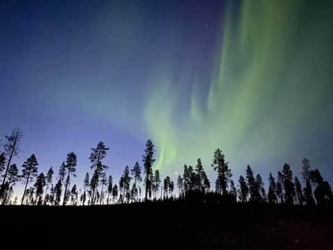 Casa de campo entre as luzes do norte à noite e ao pôr do sol.