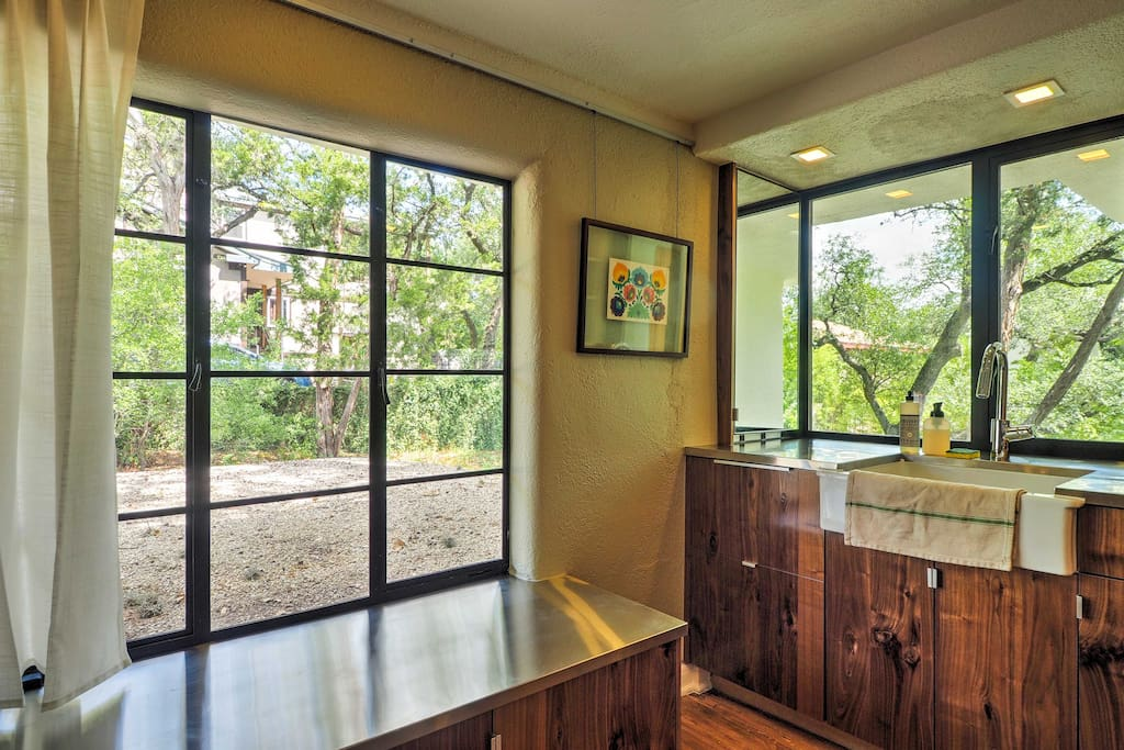 The bright fully equipped kitchen boasts vibrant treetop views!