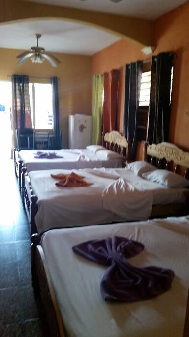 habitación con tres camas , un escritorio y una nevera con agua y cervezas disponibles