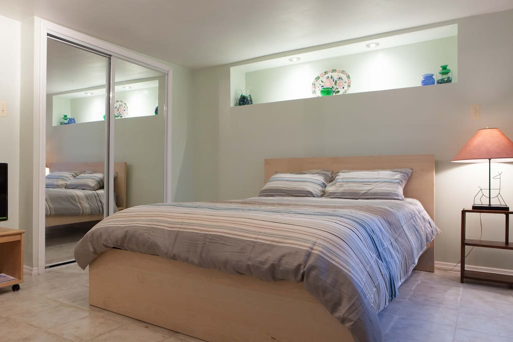 Opposite the windows on the the other side of the bed is the closet with mirrored sliding doors