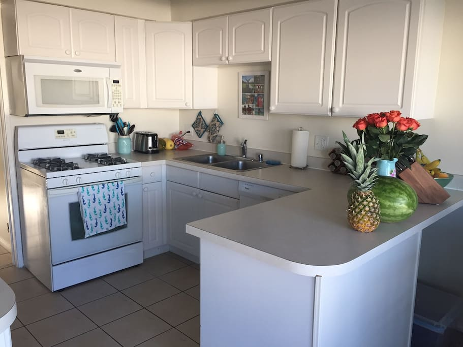 Fully equipped kitchen with refrigerator, stove tops, dishwasher, garbage disposal and oven.