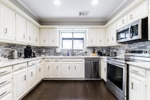 large kitchen with smart fridge smart microwave smart oven smart dishwasher and coffee machine