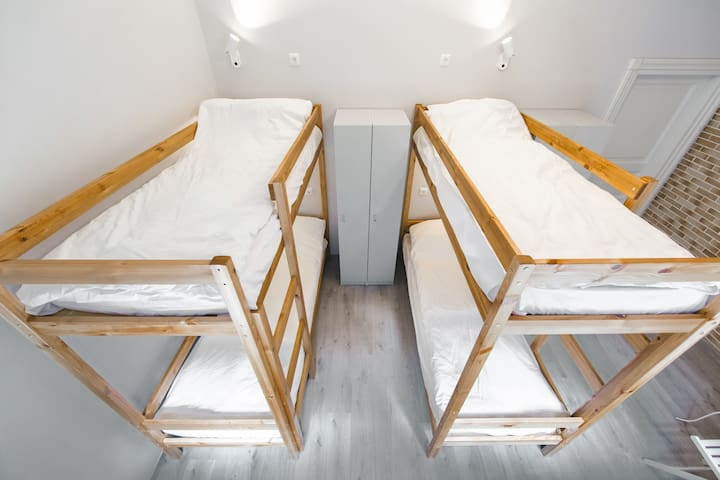 Общий вид комнаты. Четыре двухъярусных кровати, удобные ящики для хранения личных вещей.