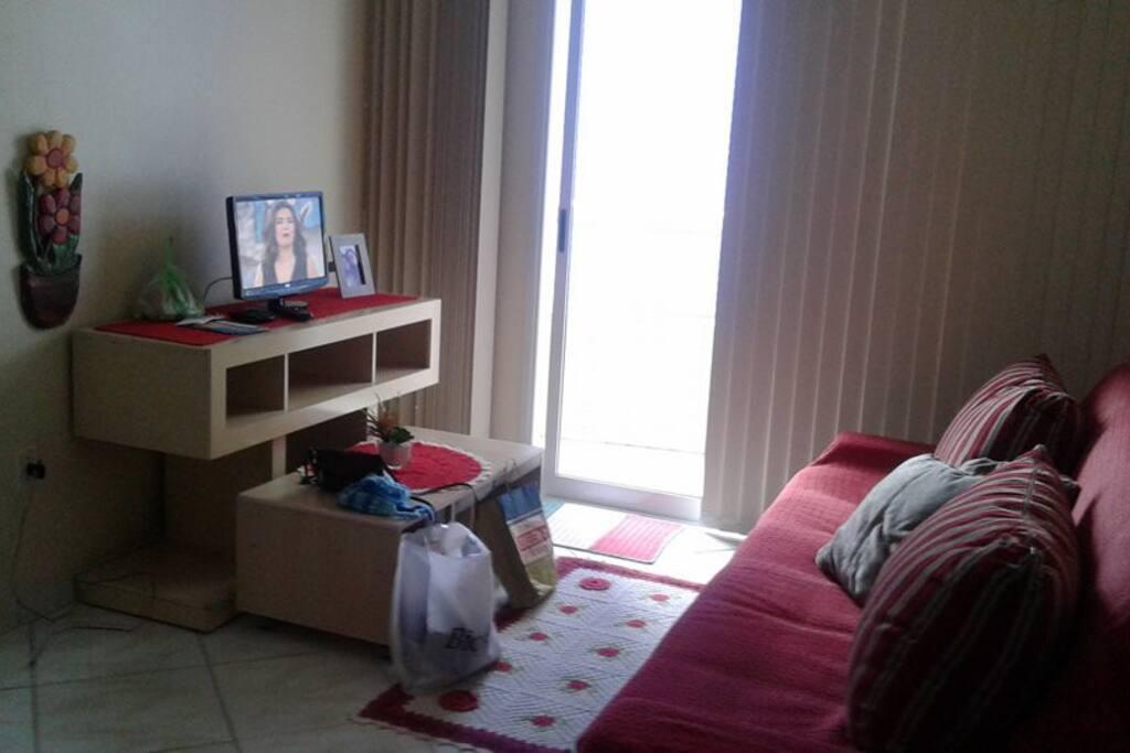 Sala com mesinha, rack e televisão