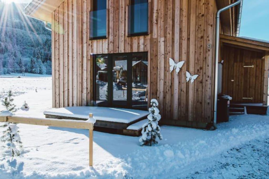 Voorkant chalet in de winter met terras bij de keuken