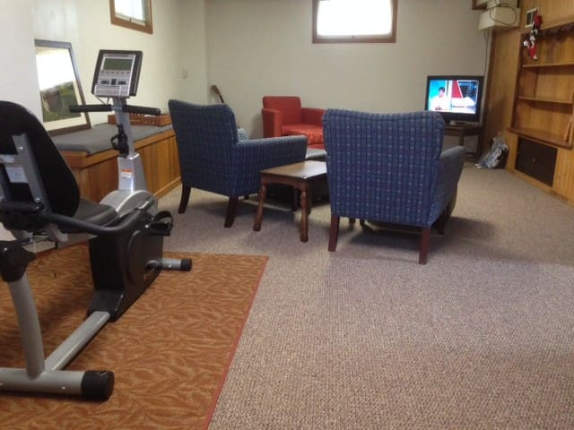 Spacious family room with TV exercise bike and yoga mats