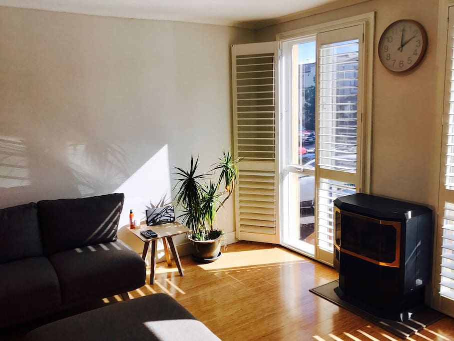 Light filled lounge room with danish style furniture, brand new reverse cycle air conditioner/heater and gas coonara fireplace.
