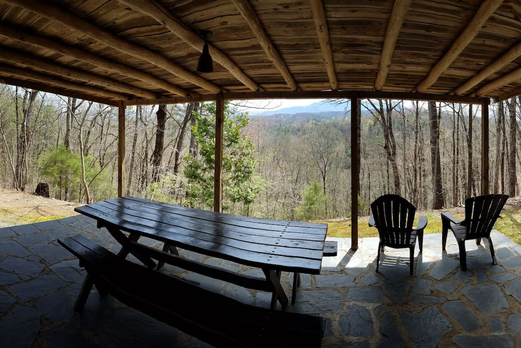The porch with dining table and benches, mountains in the distance