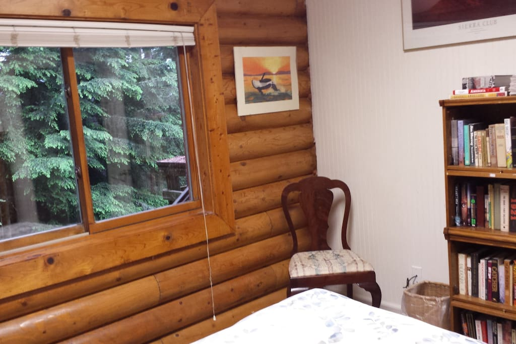 The large window in the Garden View guest room overlooks the back yard, garden, and spruce trees.