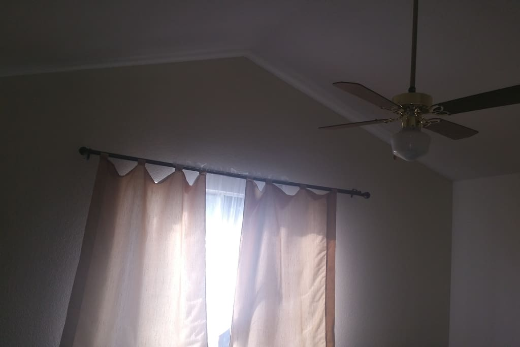 Vaulted ceiling, fan and window in the room