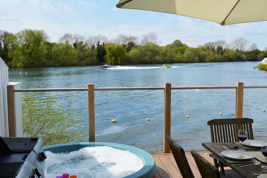 Private secure deck onto Spring Lake with hot tub, table and chairs and BBQ