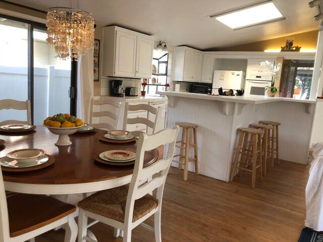The light bright white kitchen area is open and seats 6 at the table and 4 at the bar! The living, kitchen and dining are all one big open great room with french doors leading to patio!