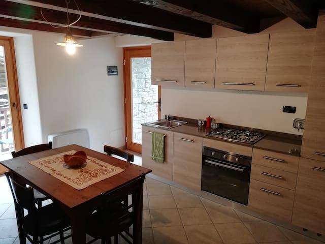 Zona giorno con cucina moderna, dotata di freezer e forno, angolo tv con divano.