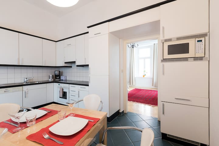 kitchen with dining area with view to 2nd bedroom with coffee machine, microwave and dishwasher