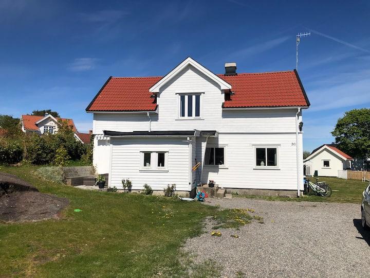 Koselig eldre hus rett ved sjøen, med huskatt