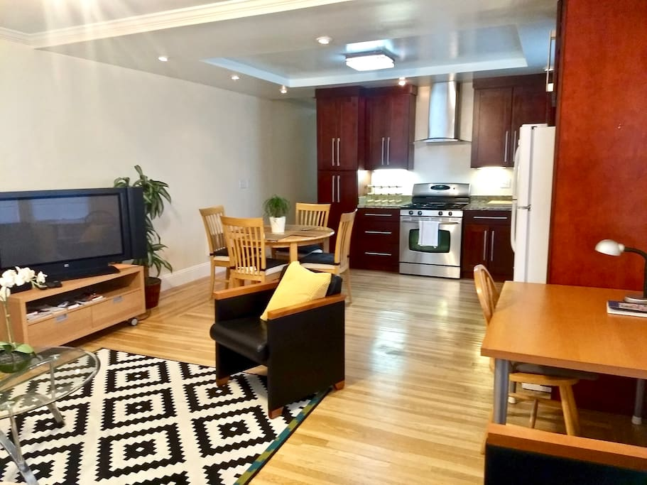 View of Living, Dining areas, and Kitchen with updated appliances, granite counters, wood floors