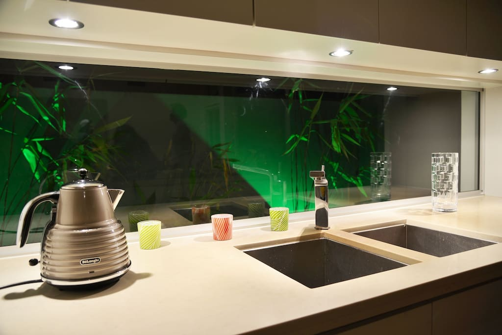 Glass splashback in kitchen with green lights outside