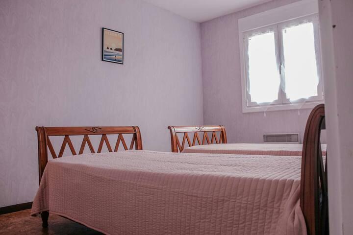 Chambre avec deux lits simples et une armoire.