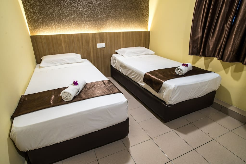 This is our Standard Twin Room. It comes with fitted bathroom, shower and WC, flat screen TV, cable TV, air-conditioning, working desk, vanity mirror, free drinking water. Bathroom amenities are provided, hair dryer and ironing facilities are on request.