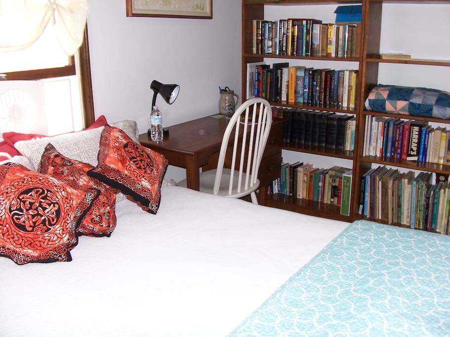 Room includes desk, two chairs, bookcase w/books