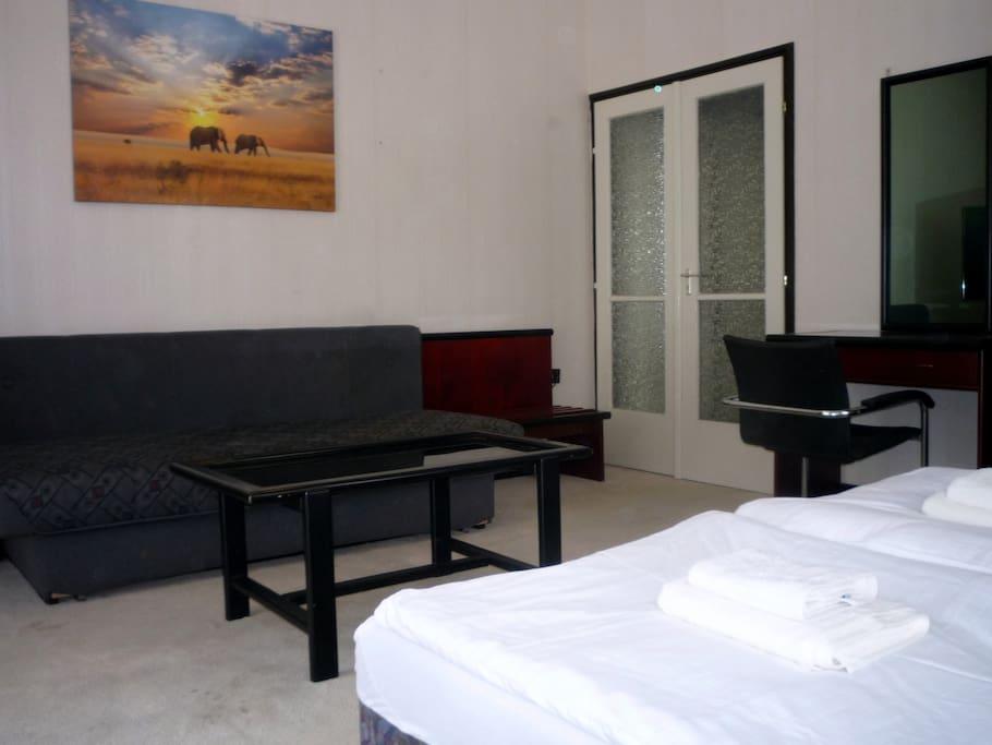Nagyszoba két külön ággyal, kétszemélyes kanapéval