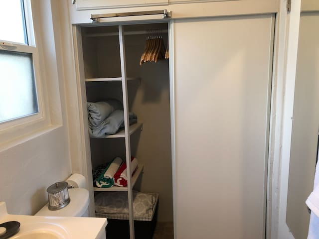 Closet with pillows for bed, beach towels and duvet