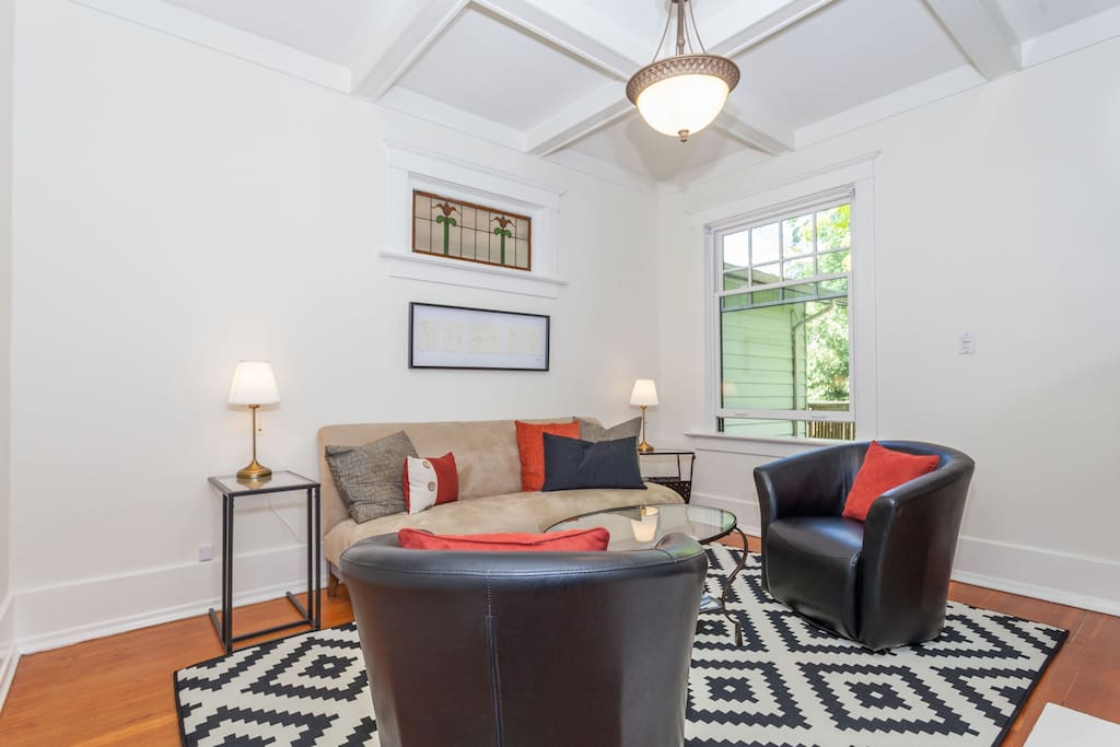 Living room with swivel chairs and comfy couch, high coffered ceilings, characteristic of 1910 house