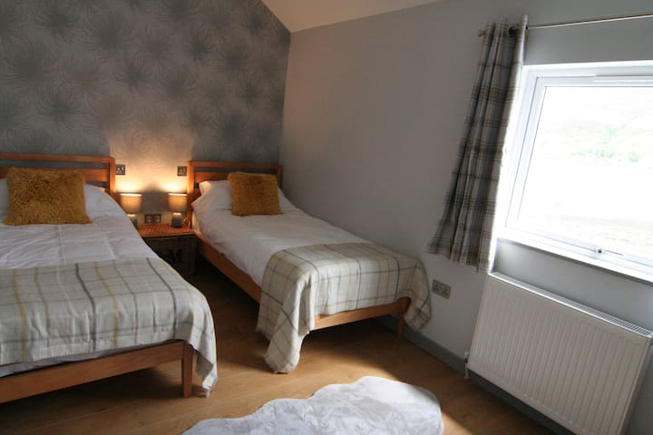 The second bedroom has twin beds, views over the Loch and is directly opposite the accessible shower room