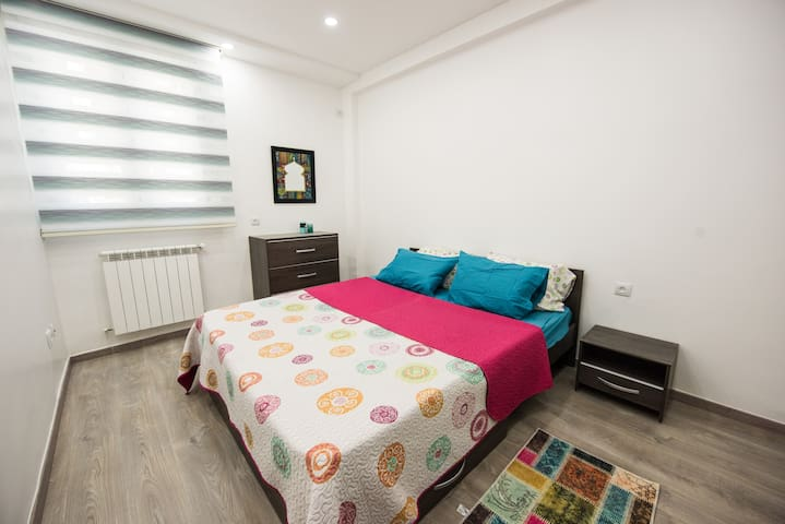 The 1st bedroom, with double size bed, nightstand, dressing, central heating, parquet floor.  Equipped with all the necessary blankets, pillows, and covers.