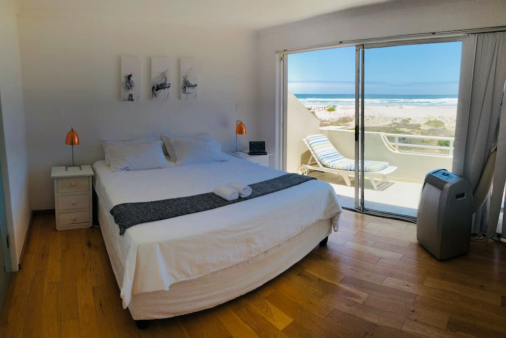 The main bedroom has a beautiful view of the ocean, and features a King Extra Size bed with white linen, and an on-suite bathroom.