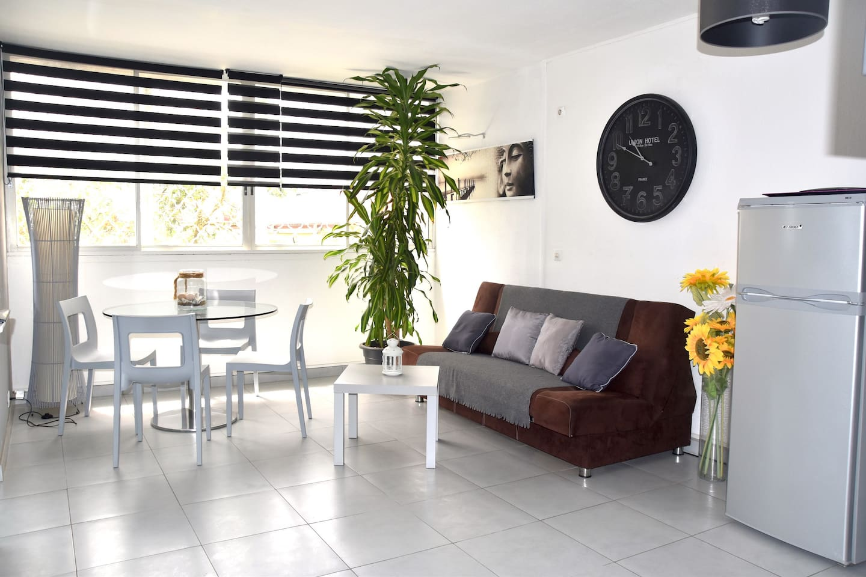 """Une pièce à vivre lumineuse sur les espaces verts de la résidence, vue mer et Marina. Idéal pour déjeuner et dîner """"en terrasse"""""""