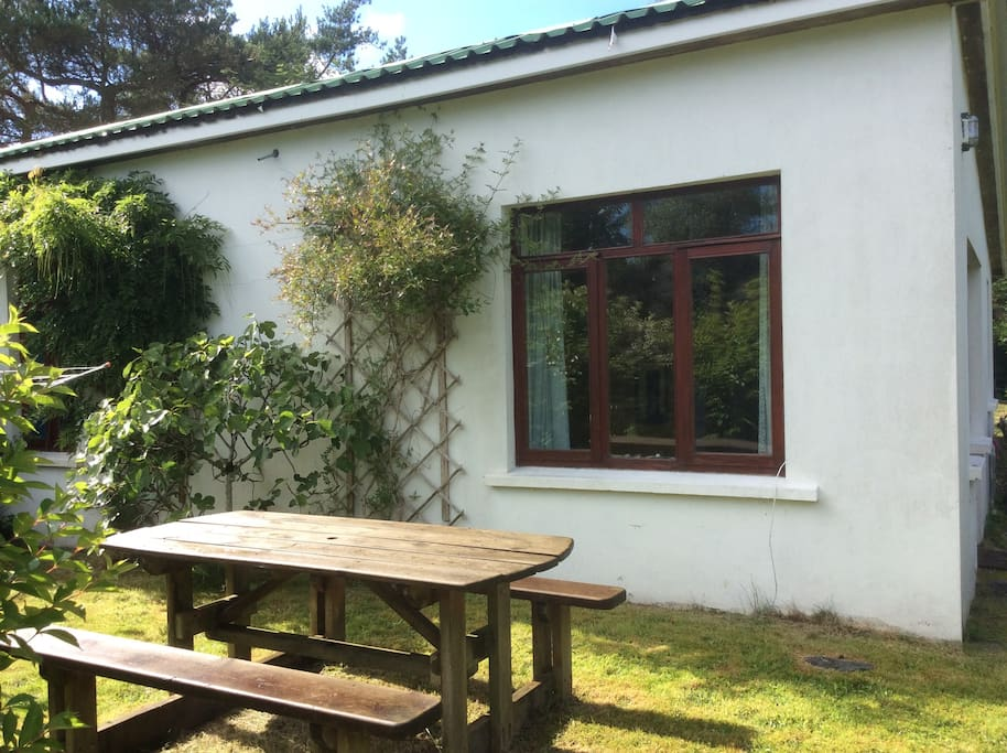 Chalet with garden and picnic bench.