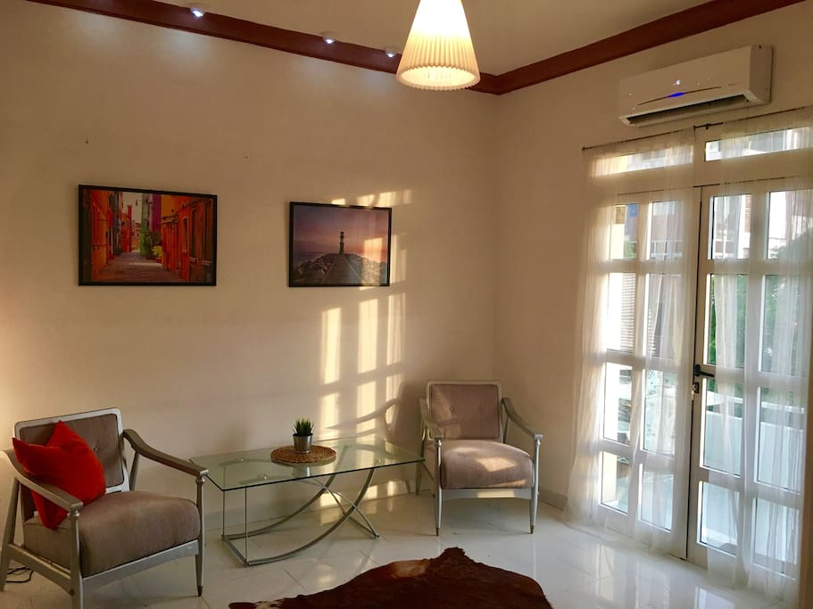 Art deco living room furniture with central AC, opens up to a large private balcony for outstanding sunsets of Havana!