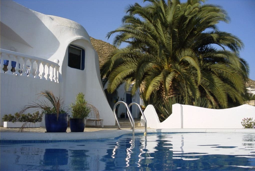 A white Gaudi house with blue surroundings