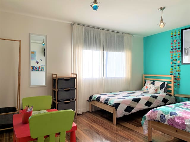 Bedroom 3, with a single and double bed. Includes hanging space, small kid's table with colouring in books, book shelf with various books from kid's to teenager, toys and night light.